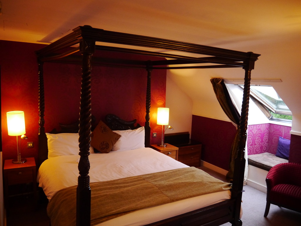 four-poster double bed with a light reading nook on the side. Clontarf Castle Hotel.